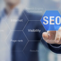 Search Engine Optimization consultant touching SEO button on whiteboard